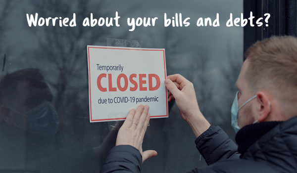 Man putting up a sign saying temorarily closed due to covid-19 - are you worried abiout paying your bills and debts now payment breaks are ending?
