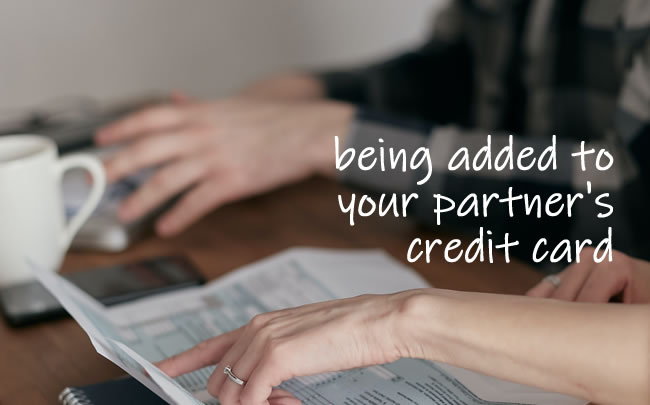 A couple looking at their finances together - will his credit score improve if he is added to his partner's credit card?