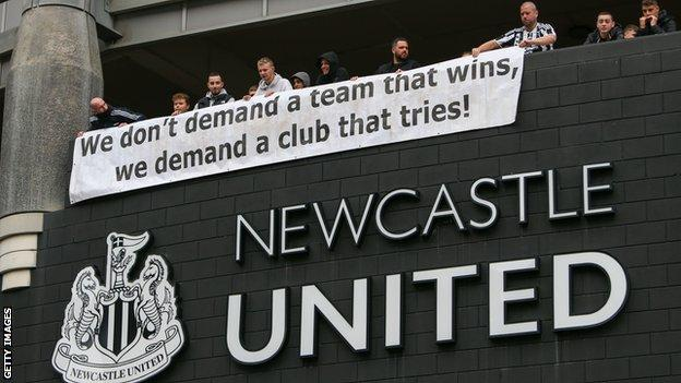 """Newcastle fans unfurl a banner that reads """"We don't demand a team that wins, we demand a club that tries!"""" after the takeoever was announced"""